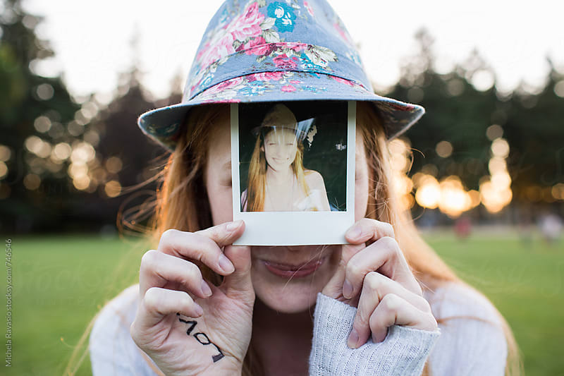 Smiling girl holding her polaroid portrait by michela ravasio for Stocksy United
