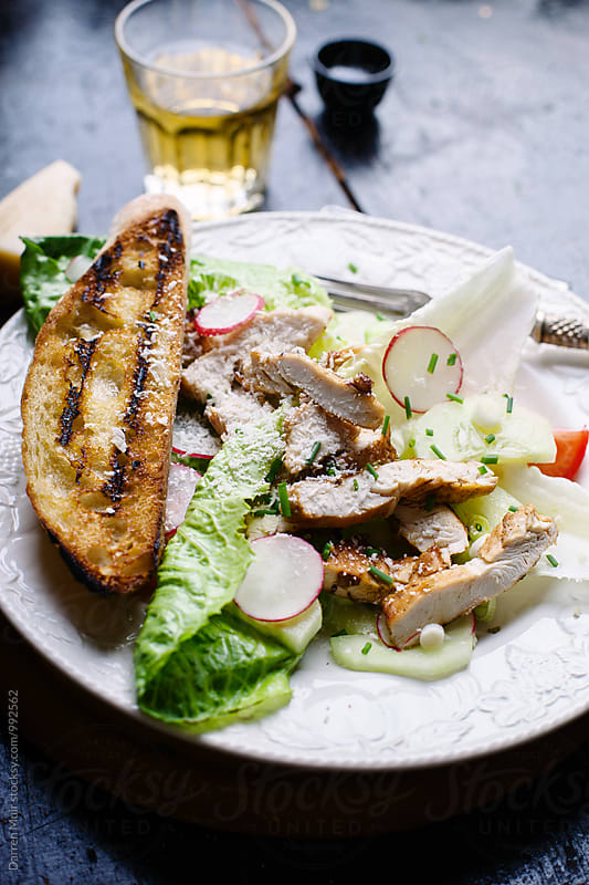 Chicken and Parmesan salad with garlic bread. by Darren Muir for Stocksy United