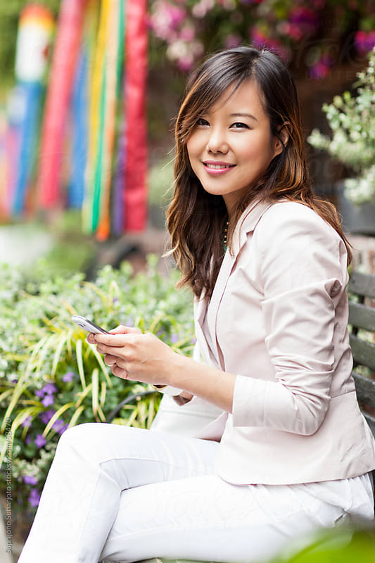 Beautiful Asian woman sitting on a bench while holding her cellp by Suprijono Suharjoto for Stocksy United