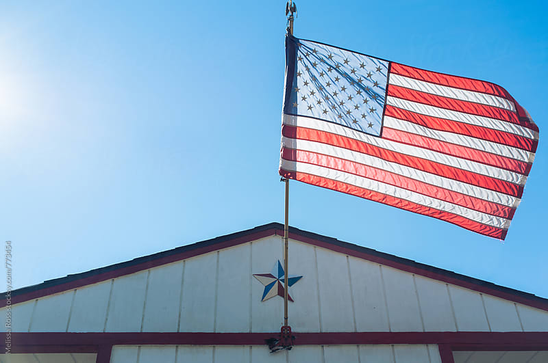 American flag waving on a sunny day. by Melissa Ross for Stocksy United