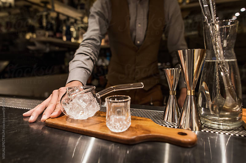 Closeup of Barman Preparing Elaborate Cocktail in Stylish Dark Bar by VISUALSPECTRUM for Stocksy United
