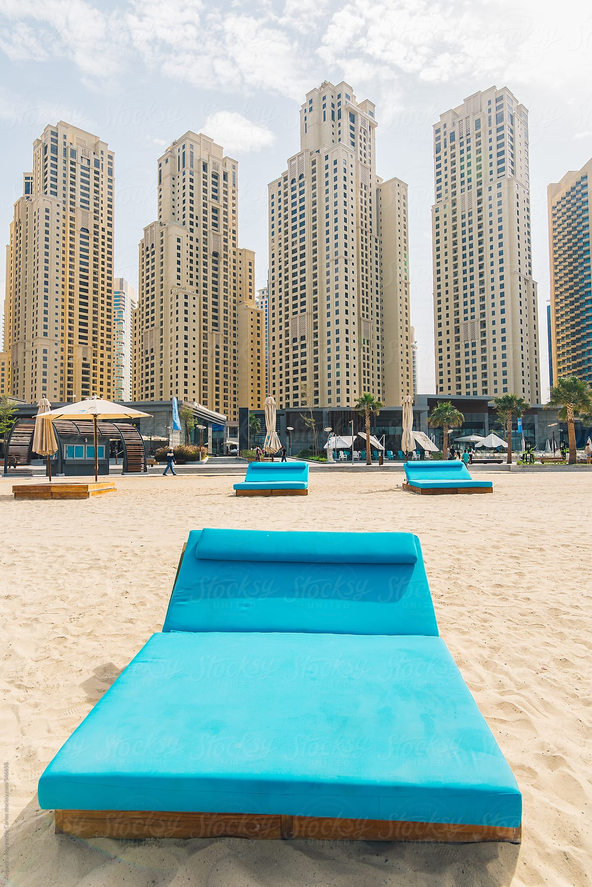 Blue Sunbed On The Beach And City Buildings On The Background Marina Beach Dubai United Arab Emirates By Alejandro Moreno De Carlos Stocksy United