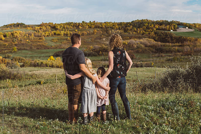 Modern family standing together against autumn landscape by Carey Shaw for Stocksy United