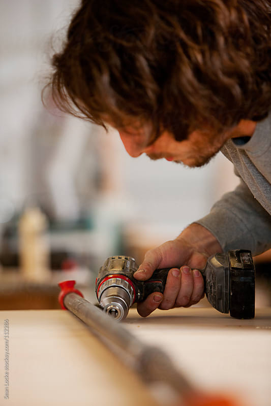 Woodworking: Man Using Drill To Screw Anchors In by Sean Locke for Stocksy United