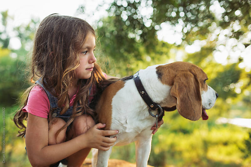 Girl and a beagle by Dejan Ristovski for Stocksy United