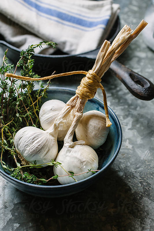 Garlic bulbs and thyme in a bowl. by Darren Muir for Stocksy United