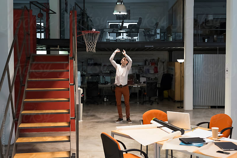 Young businessman playing in a cool office by Simone Becchetti for Stocksy United