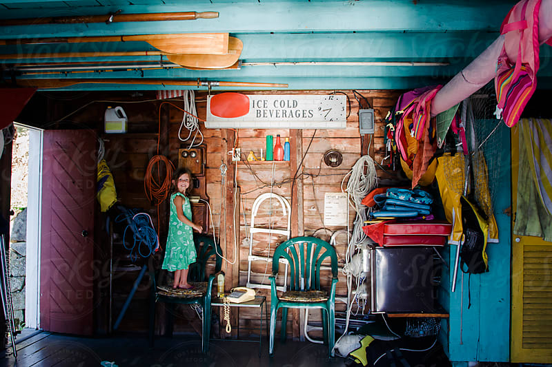 A little girl plays in an old boat house on a hot summer day. by Holly Clark for Stocksy United
