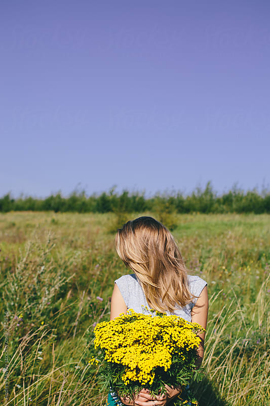 Blonde girl holding big bouquet of wildflowers at a field by Andrey Pavlov for Stocksy United