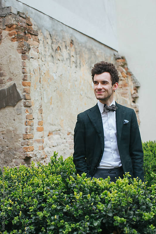 Outdoor Portrait of Young Smiling Caucasian Man in Green Jacket and Bow Tie by VISUALSPECTRUM for Stocksy United