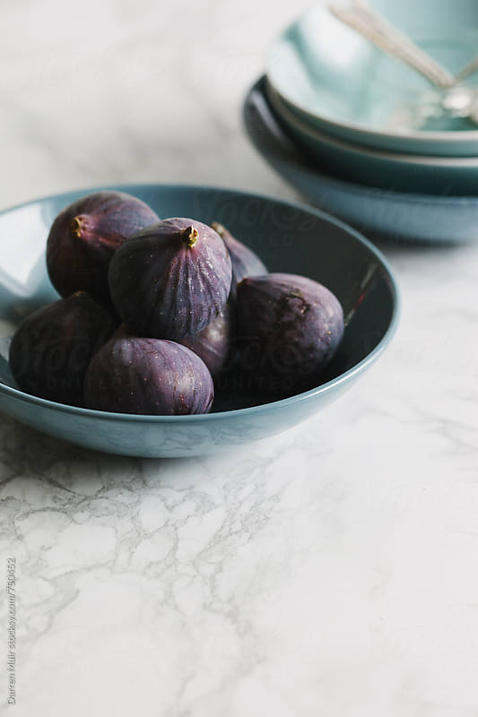 Ripe seasonal figs in a blue bowl on a marble surface. by Darren Muir for Stocksy United
