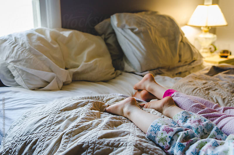Bare feet of two kids lying on a bed in their pajamas by Lindsay Crandall for Stocksy United