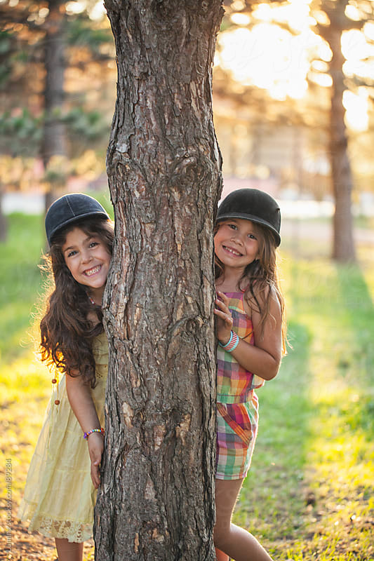 Smiling Girls Behind a Tree by Lumina for Stocksy United