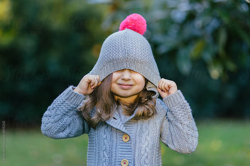 Portrait of a cute young girl pulling a hood over her face by Jakob for Stocksy United