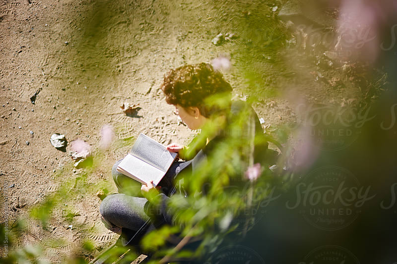 Young woman reading in a park by Martí Sans for Stocksy United