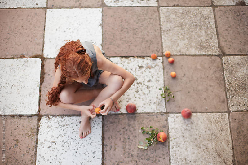 Young beautiful girl with fruit in a romantic mood by Miquel Llonch for Stocksy United