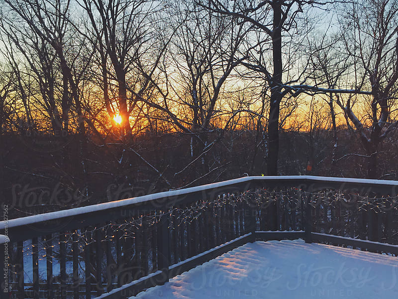 Snowy Sunset Over Woods from Residential Home Deck by Brian McEntire for Stocksy United