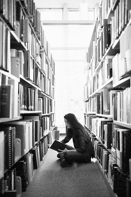 Young asian woman reading in library by Rob and Julia Campbell for Stocksy United