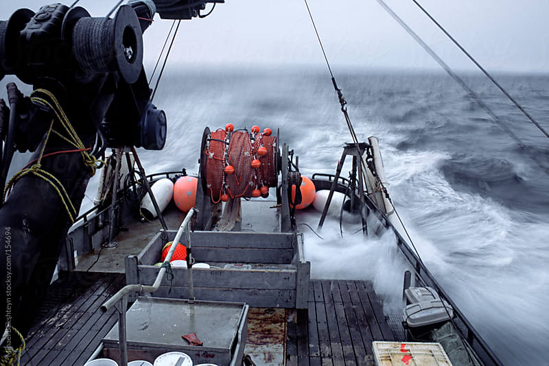 A small boat under steam in open ocean with waves rolling over its deck by Mihael Blikshteyn for Stocksy United