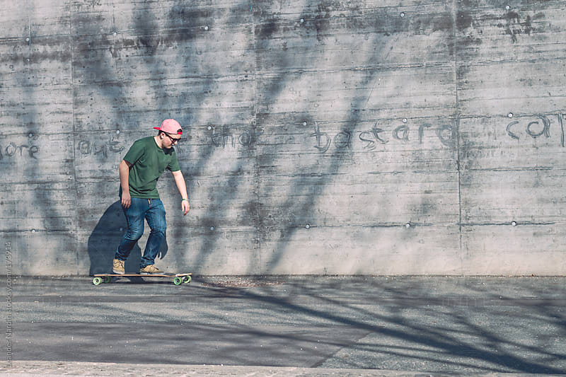 Teenager skates with  longboard in front of a wall by Leander Nardin for Stocksy United