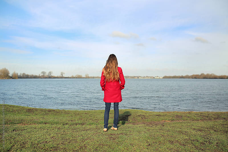 Woman in a red coat standing in front of a lake by Lucas Ottone for Stocksy United