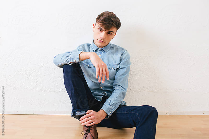 Portrait of a young man wearing denim clothes sitting. by BONNINSTUDIO for Stocksy United