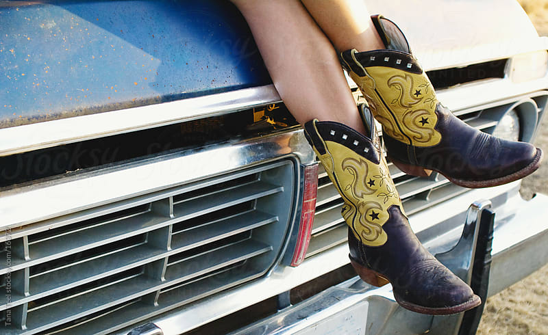 A young woman's cowboy boots hanging down from pickup hood.  by Tana Teel for Stocksy United