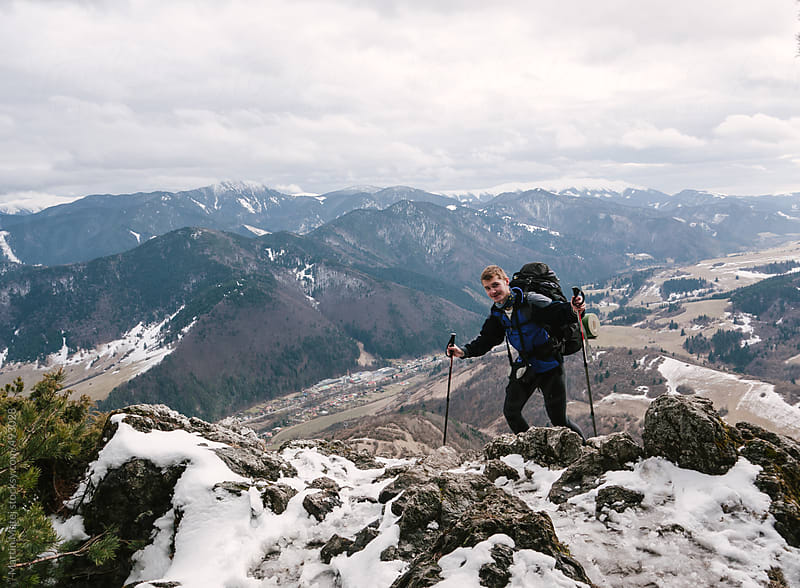 Happy backpacker standing on snowy rocks by Martin Matej for Stocksy United