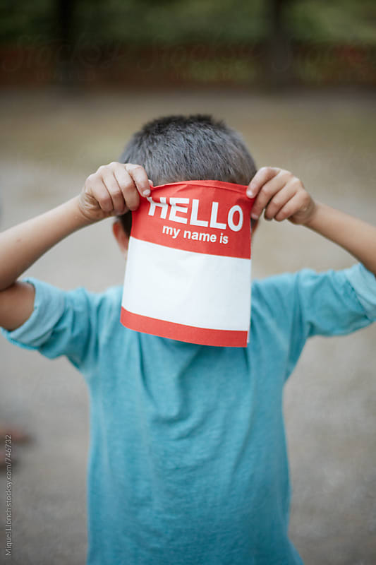 Young boy hiding his face behind a paper napkin with the word hello my name is by Miquel Llonch for Stocksy United