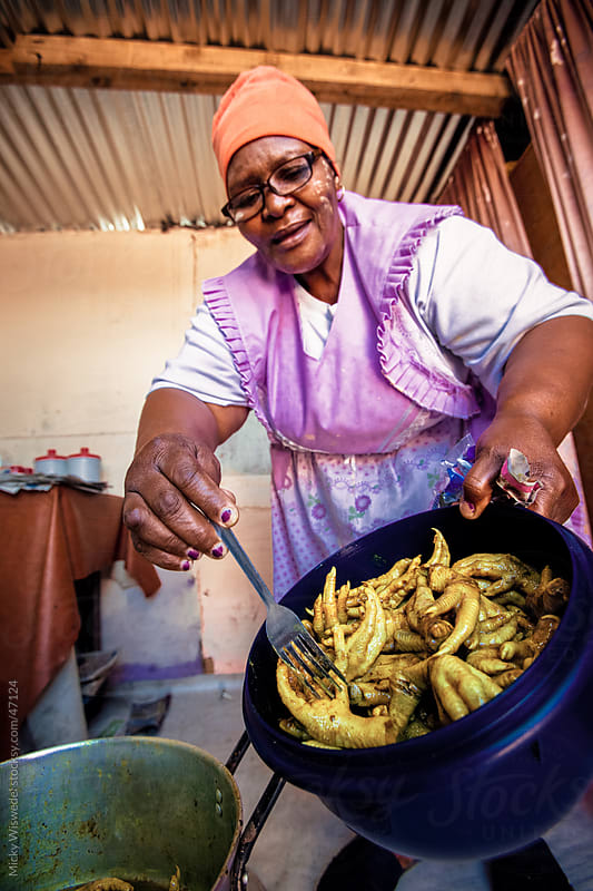 African woman preparing township food by Micky Wiswedel for Stocksy United