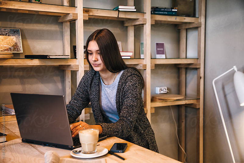 Young woman sitting in cafe and using her laptop by Danil Nevsky for Stocksy United