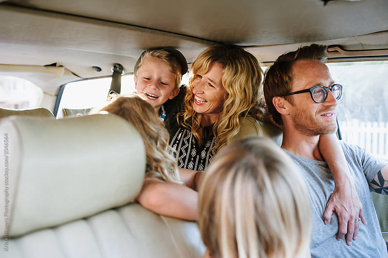Happy family sitting in car on roadtrip by Kristin Rogers Photography for Stocksy United