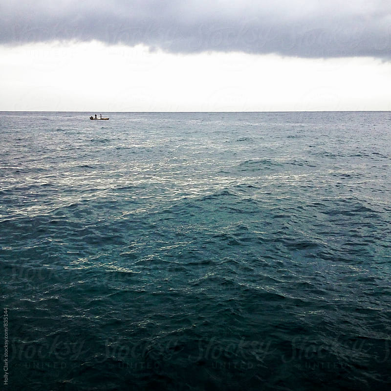 A tiny fishing boat in the vast Caribbean Sea beneath a layer of clouds. by Holly Clark for Stocksy United