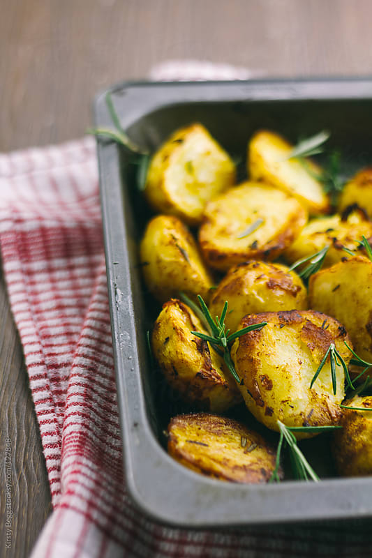 Roast potatoes with rosemary in roasting tin by Kirsty Begg for Stocksy United