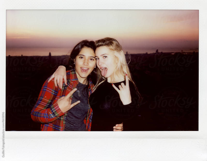 Two female friends showing horns and sticking out tongues by Guille Faingold for Stocksy United