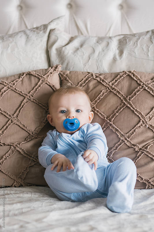 Baby sitting on a bed with his pacifier by Ania Boniecka for Stocksy United