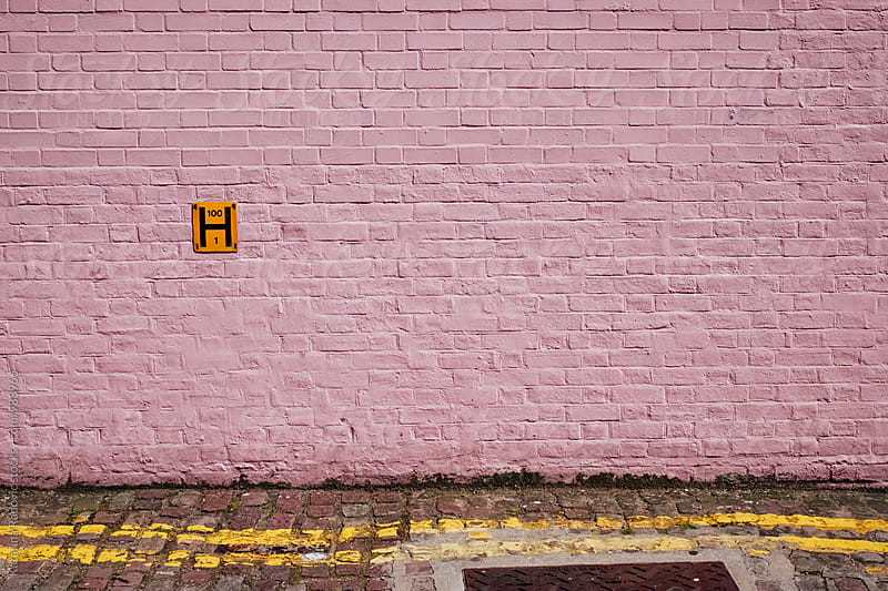Pastel Pink Brick Wall With a Yellow Sign by Katarina Radovic for Stocksy United