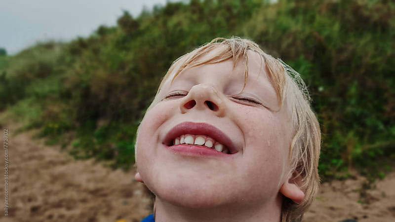 Happy smiling little boy in the rain by sally anscombe for Stocksy United