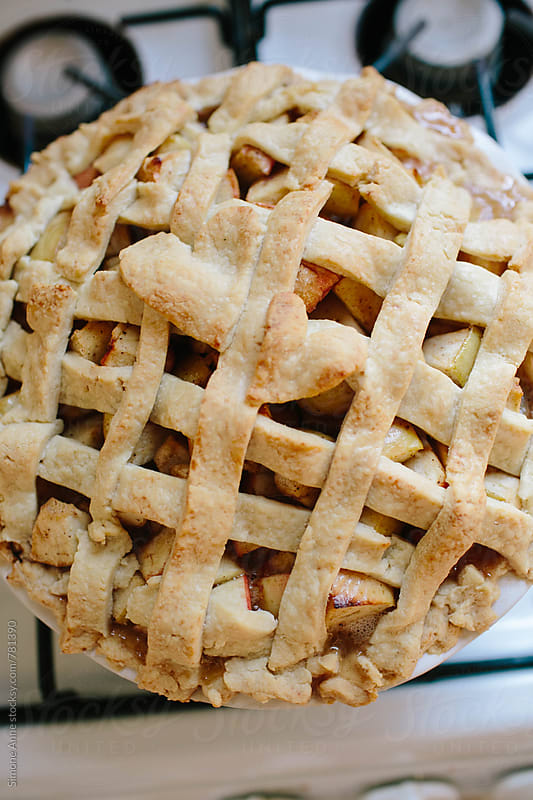 Baked apple pie sits on stove top by Simone Anne for Stocksy United