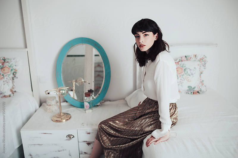 Fashionable young woman sitting on the bed by Jovana Rikalo for Stocksy United