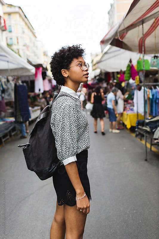 Woman walking through the market stalls by michela ravasio for Stocksy United