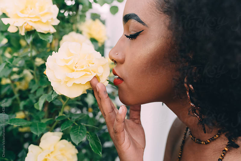 A young black woman smelling a yellow rose