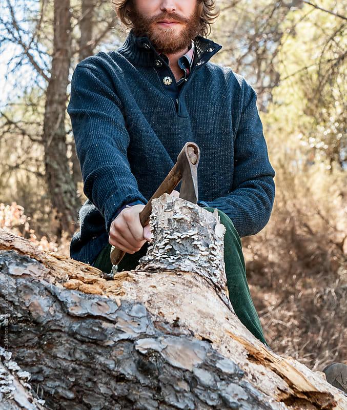 Bearded man chopping wood in the forest by Marta Muñoz-Calero Calderon for Stocksy United