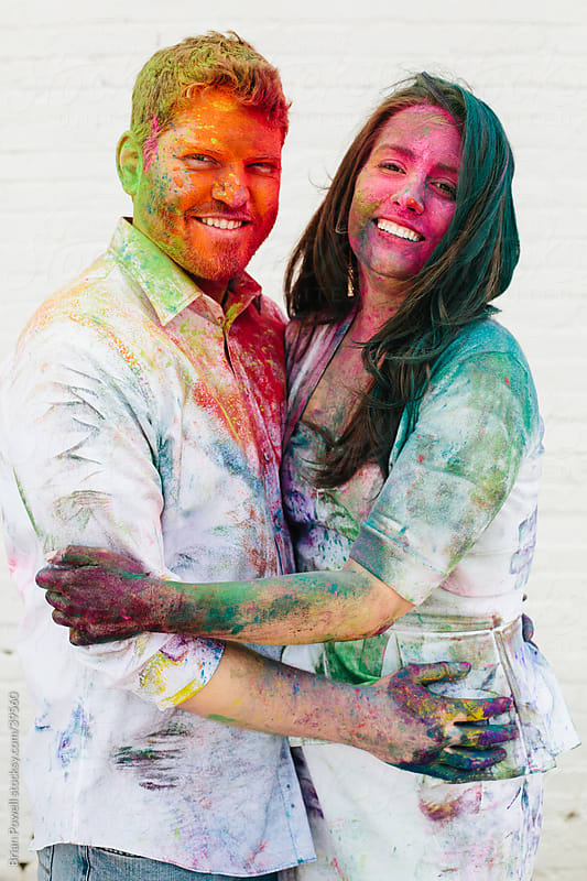 happy couple covered in Holi paint by Brian Powell for Stocksy United
