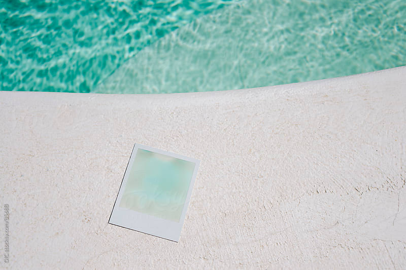 Blue polaroid against water by GIC for Stocksy United