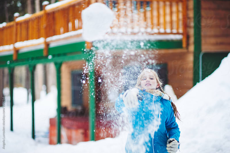 Girl throwing a snowball directly at camera by Angela Lumsden for Stocksy United