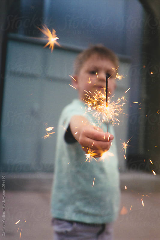Young boy holding a sparkler by Cameron Whitman for Stocksy United