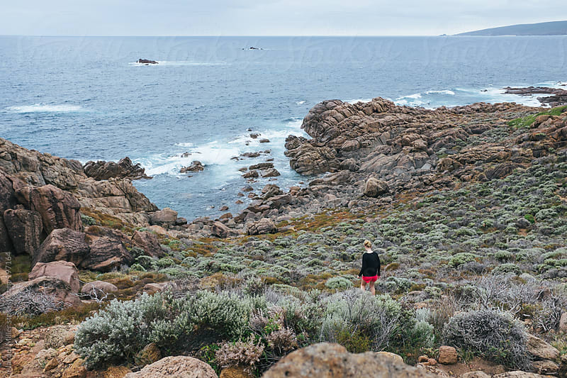 Girl walking down a hill, over a bush terrain, toward the ocean by Jacqui Miller for Stocksy United