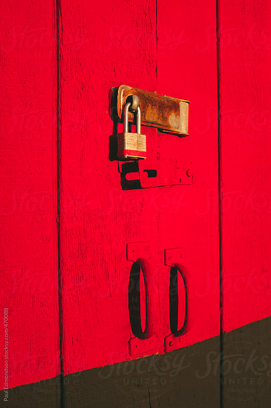 Padlock on brightly colored building door by Paul Edmondson for Stocksy United