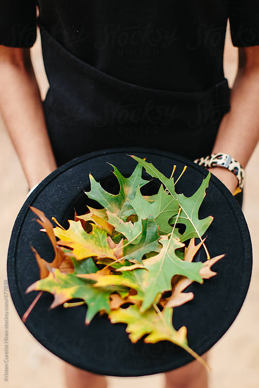 A woman holding a fedora full of leaves that fell on the ground by Kristen Curette Hines for Stocksy United